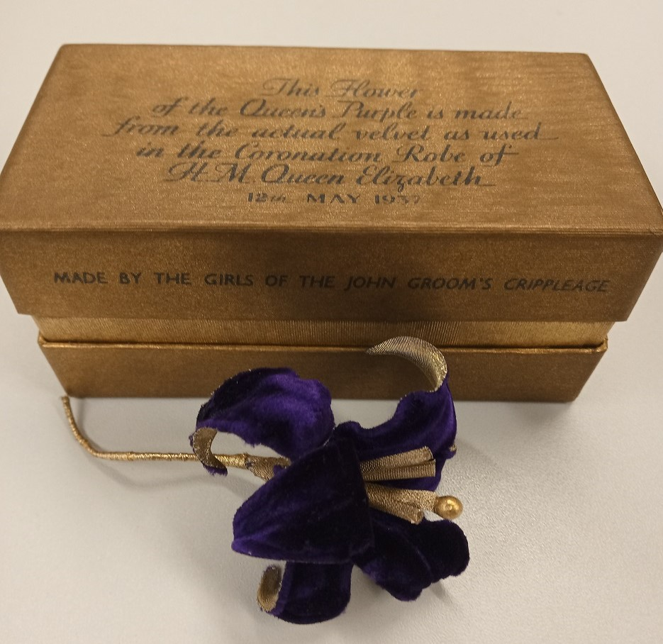 Vivid purple and gold artificial flower made from Queen Elizabeth's 1937 coronation robe by the Girls of the John Groom's Crippleage