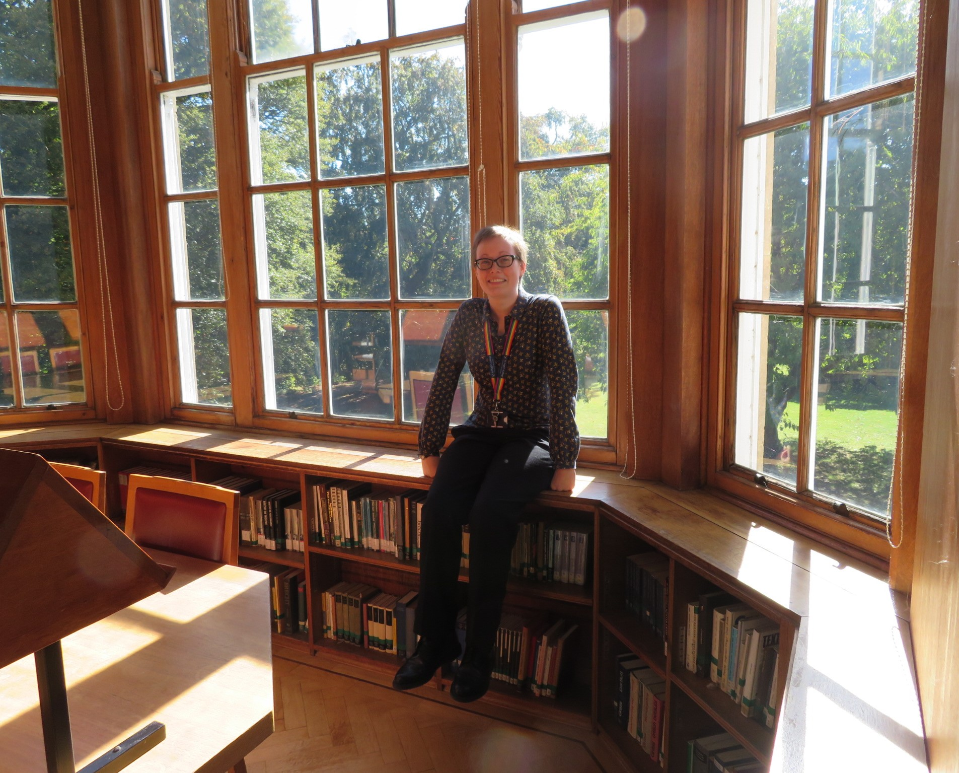 Me sitting on a window ledge in the Upper Reading Room. Large windows behind me. Books on shelves underneath the window ledge.