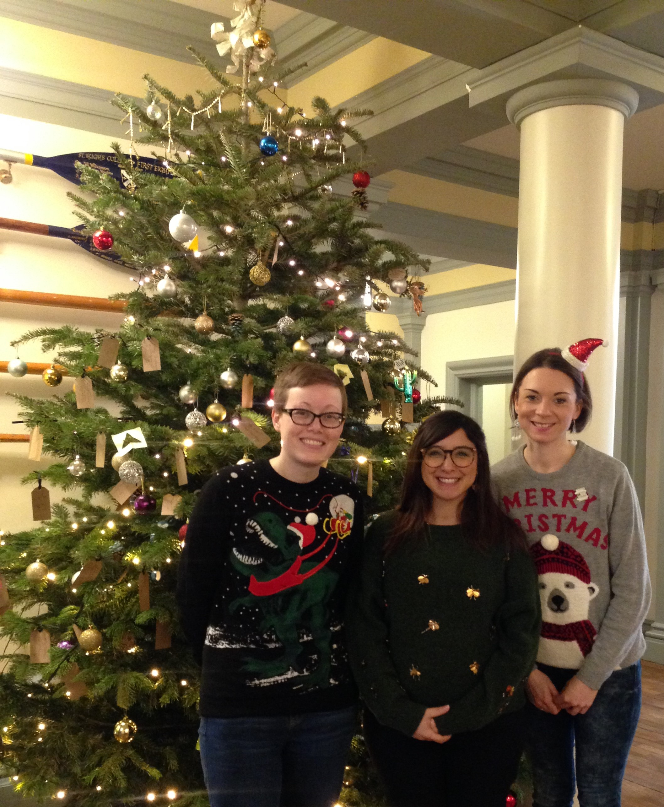 The library team, wearing Christmas jumpers, standing in front of a Christmas tree.