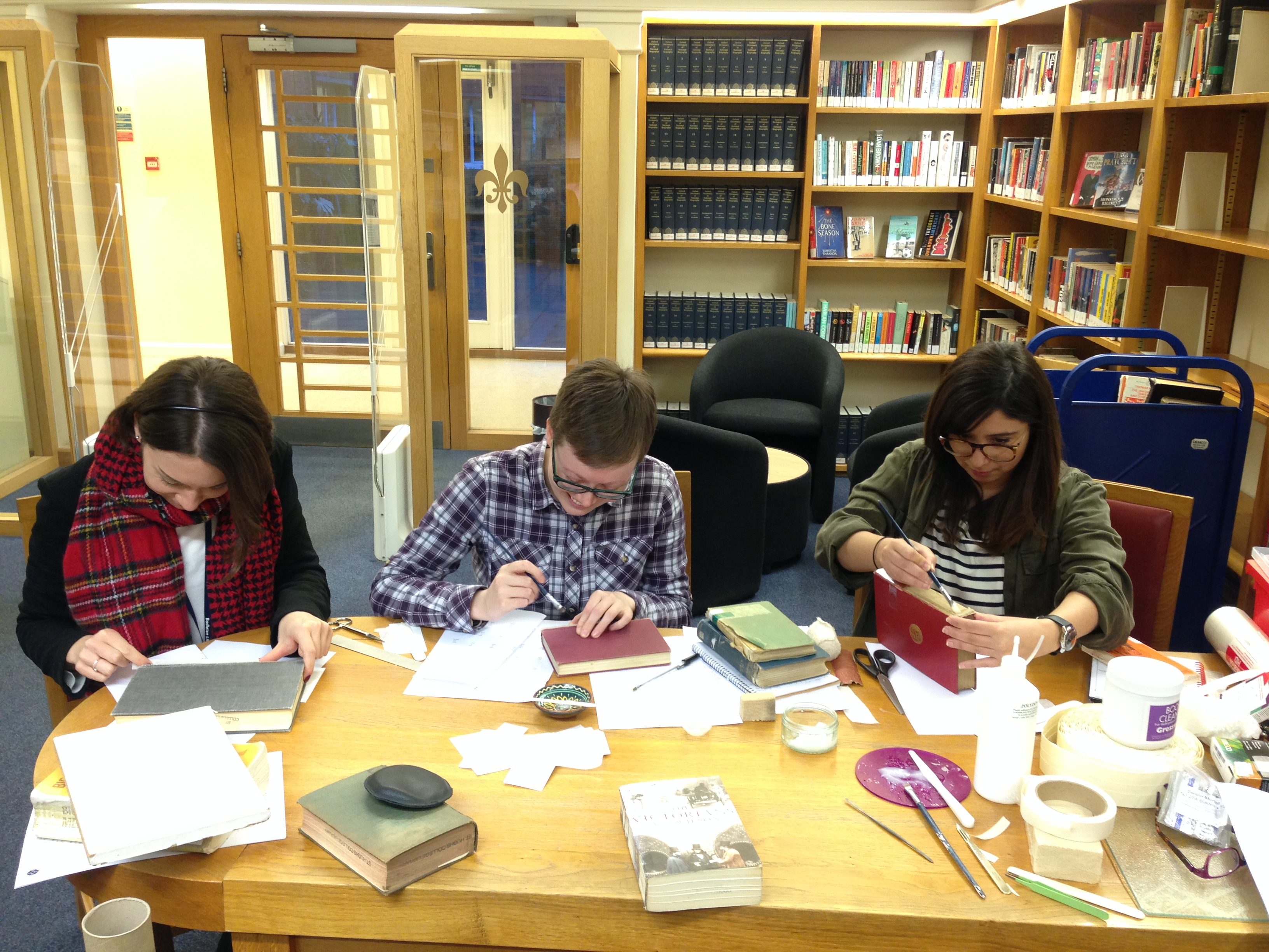 The library team sit at a table repairing books.