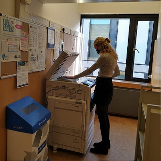 Naomi stands at a PCAS machine scanning a book