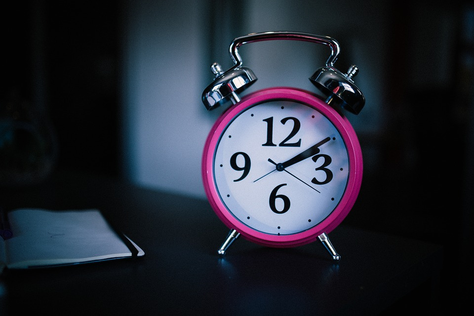 Image of a pink alarm clock on a table.