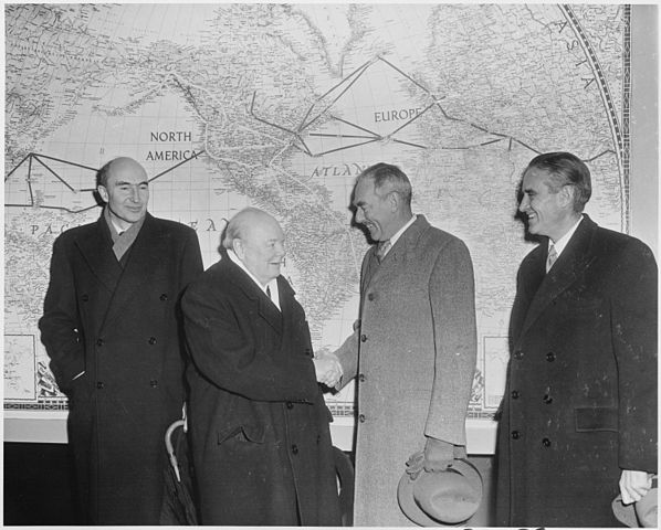 Winston Churchill shaking hands in front of map