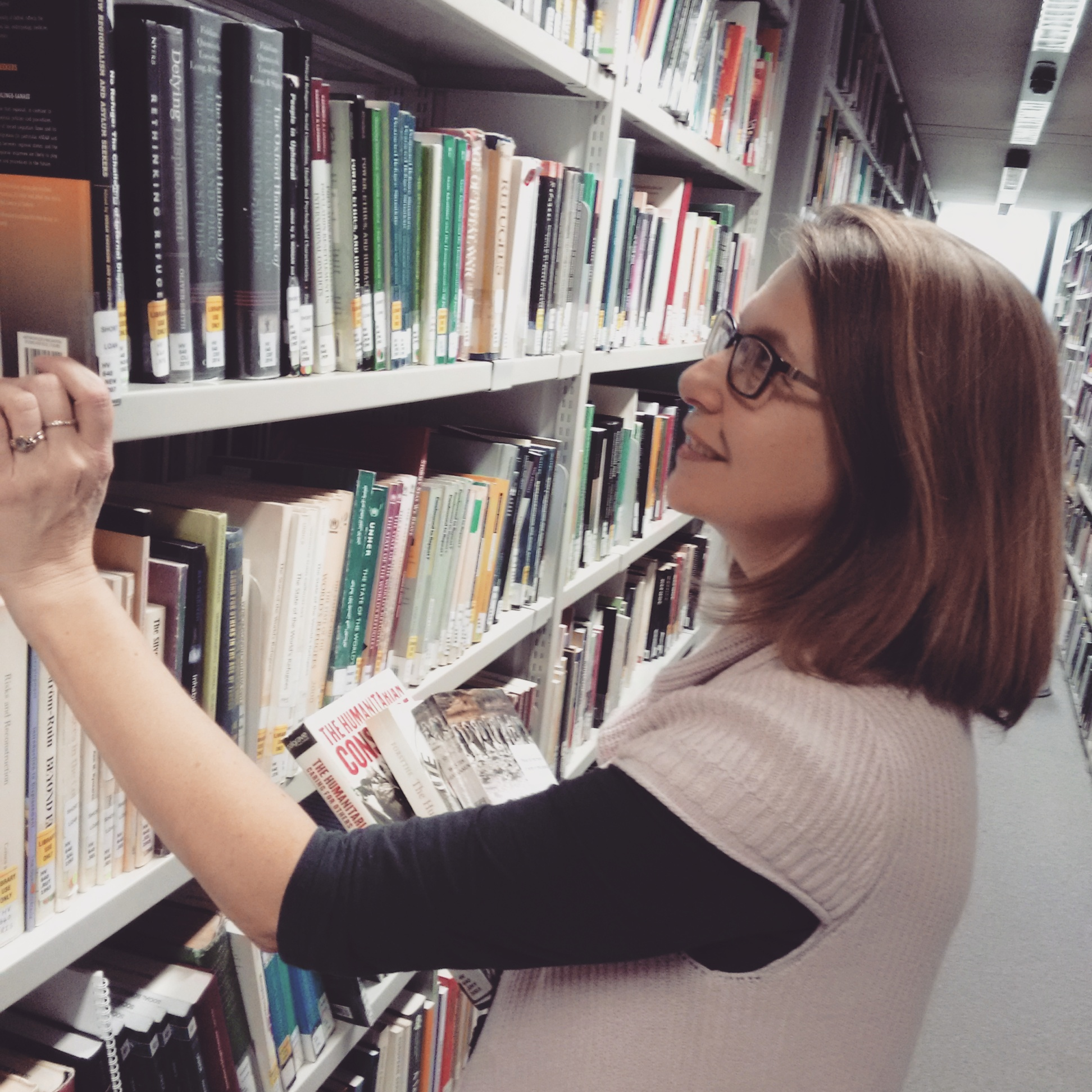 Image of Subject Consultant Sarah Rhodes selecting books from the book shelves in the Bodleian Social Science Library