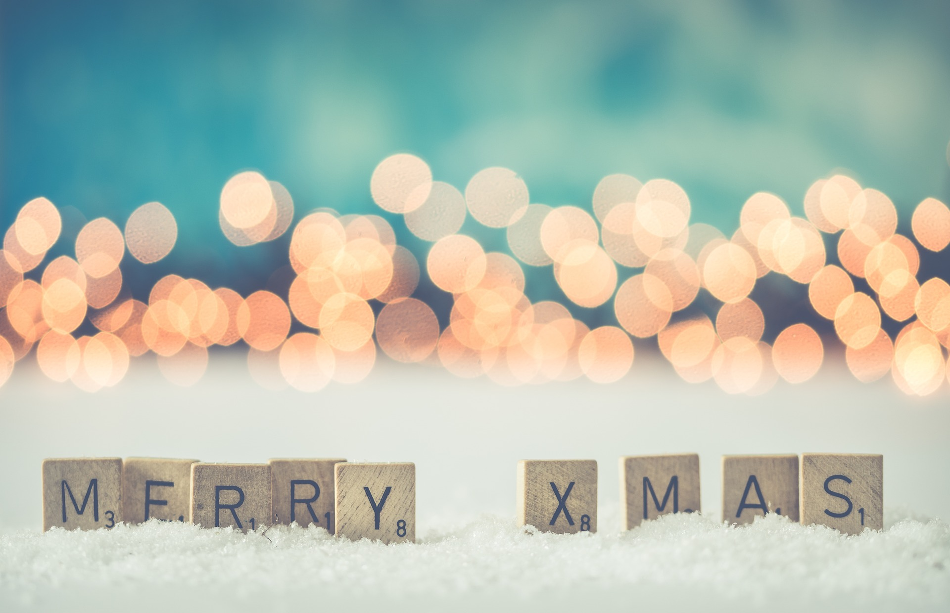 Letters in the snow on wooden scrabble tiles spelling out Merry Christmas with twinkling lights in the background