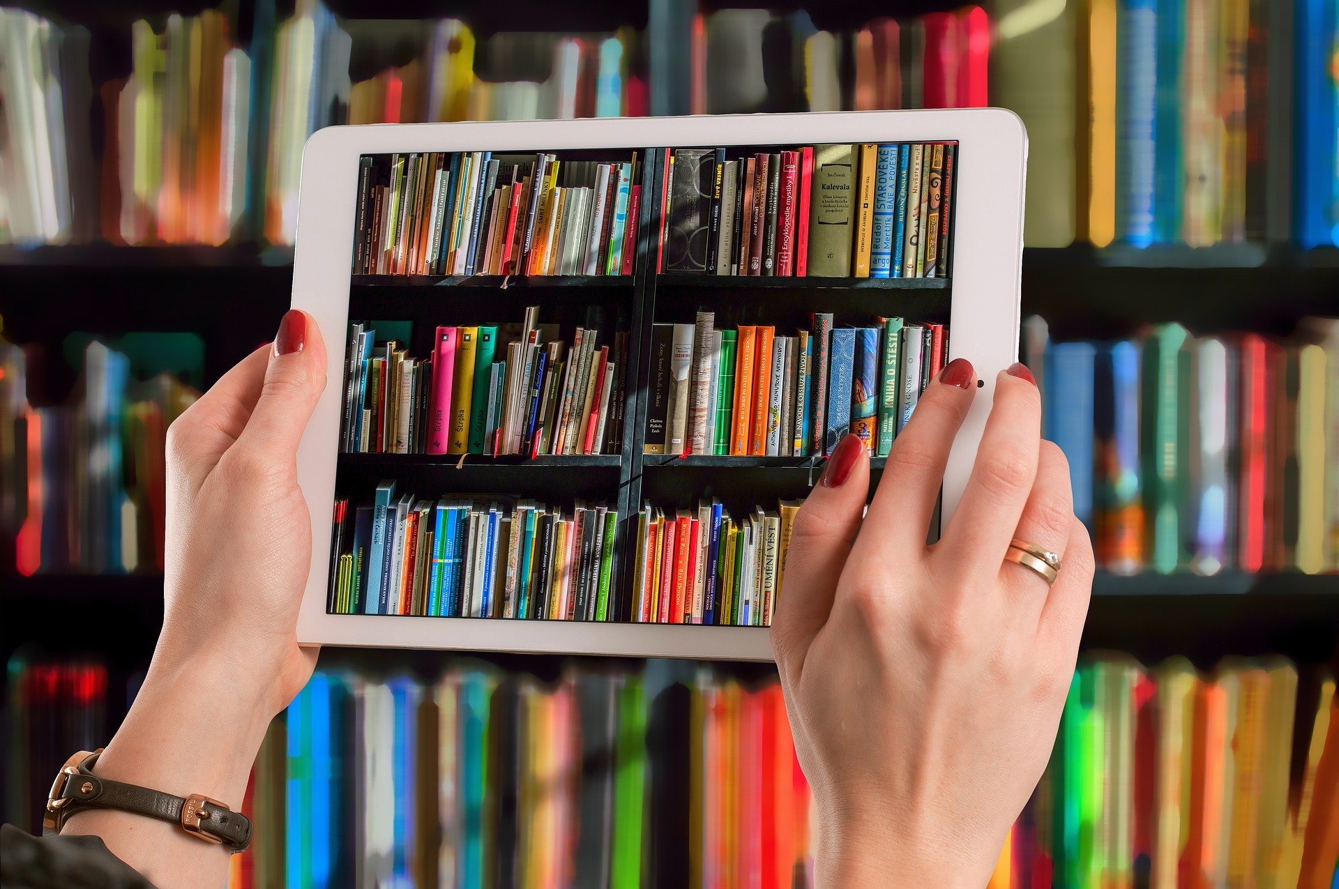 A close of up of a womans hands holding a tablet with an image of book shelves on it, in the background are books on shelves.
