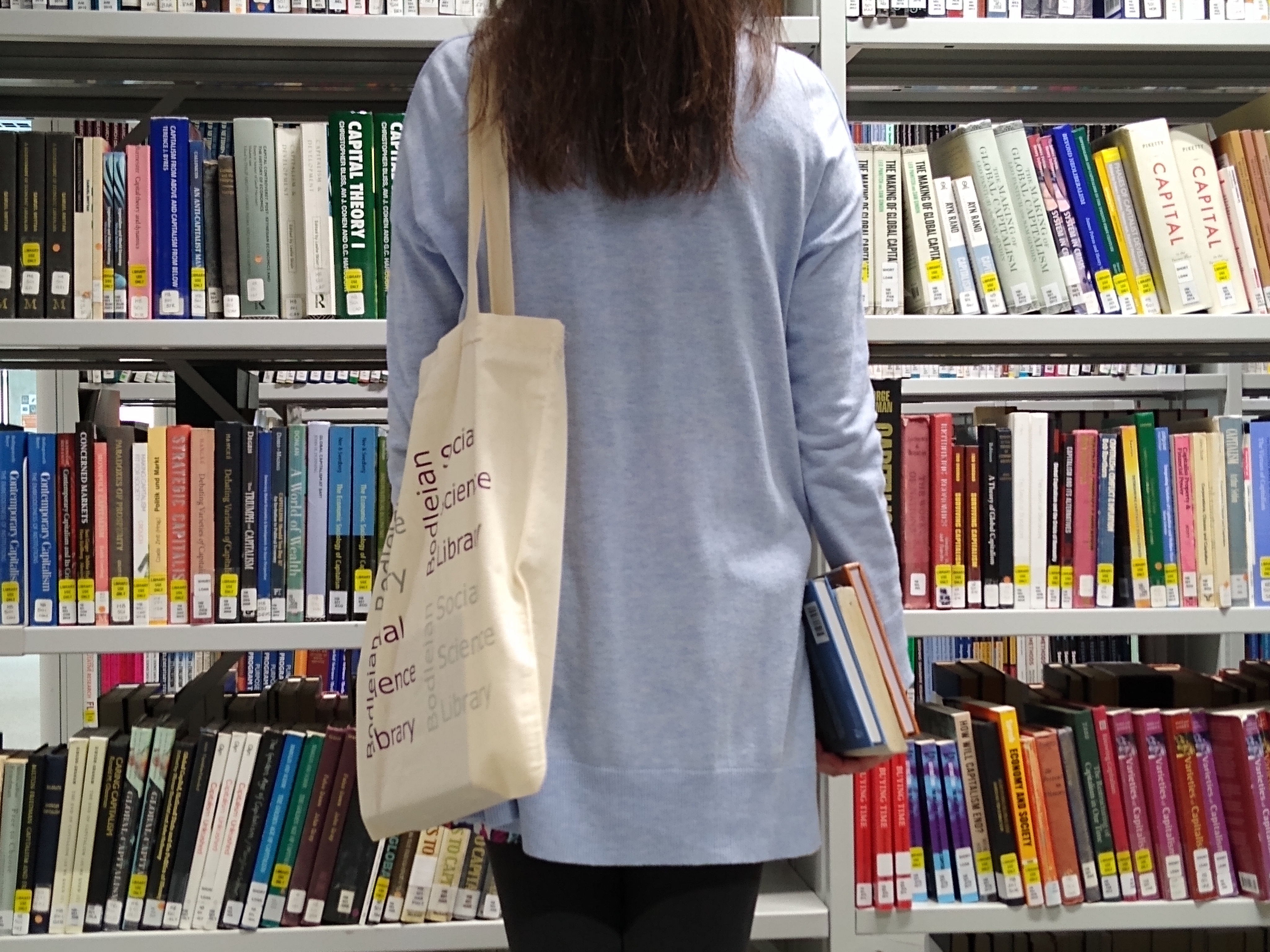 The back view of a person carrying some books and with an SSL bag over their shoulder, stood in front of some book shelves.
