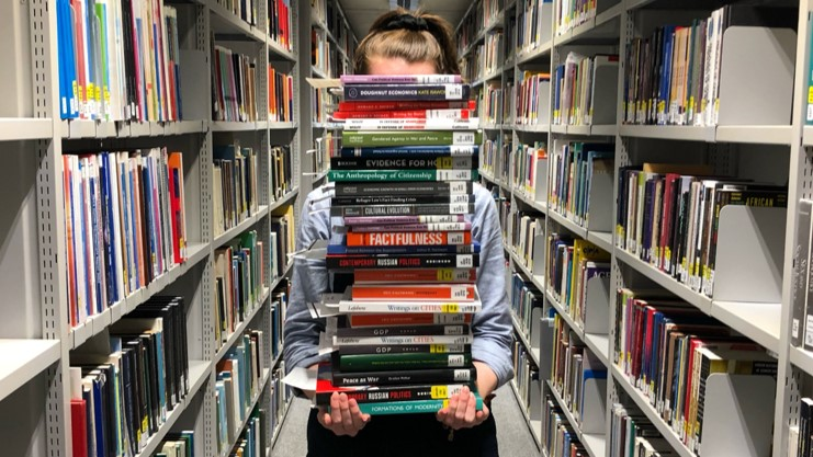 Women stood in the central aisle of 2 library books shelves holding a pile of books that is so tall it obscures her face.