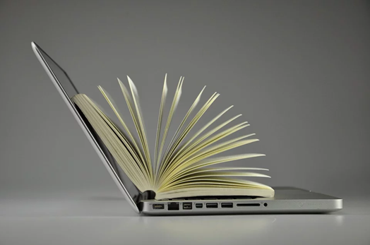 Side profile of an open laptop with a book on top of it with the pages splayed