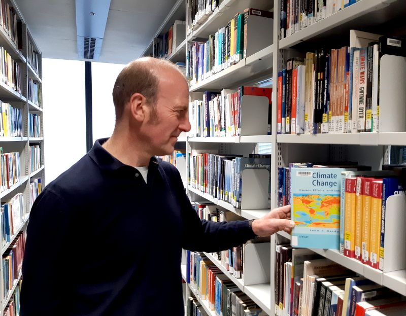 Subject Consultant Andy Kernot stood by some book shelves in the SSL selecting a geography book