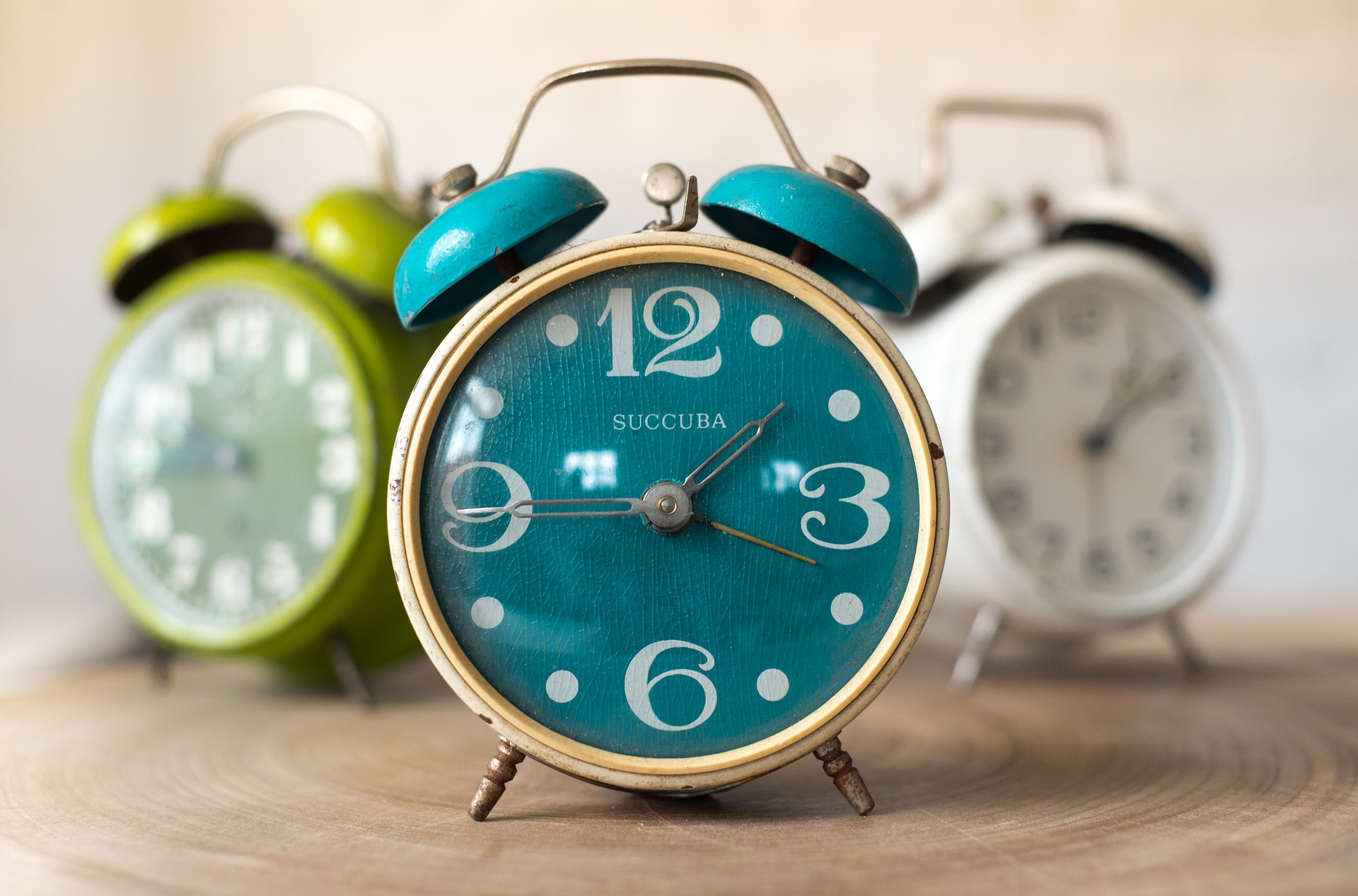 3 brightly coloured alarm clocks sat on a wooden service