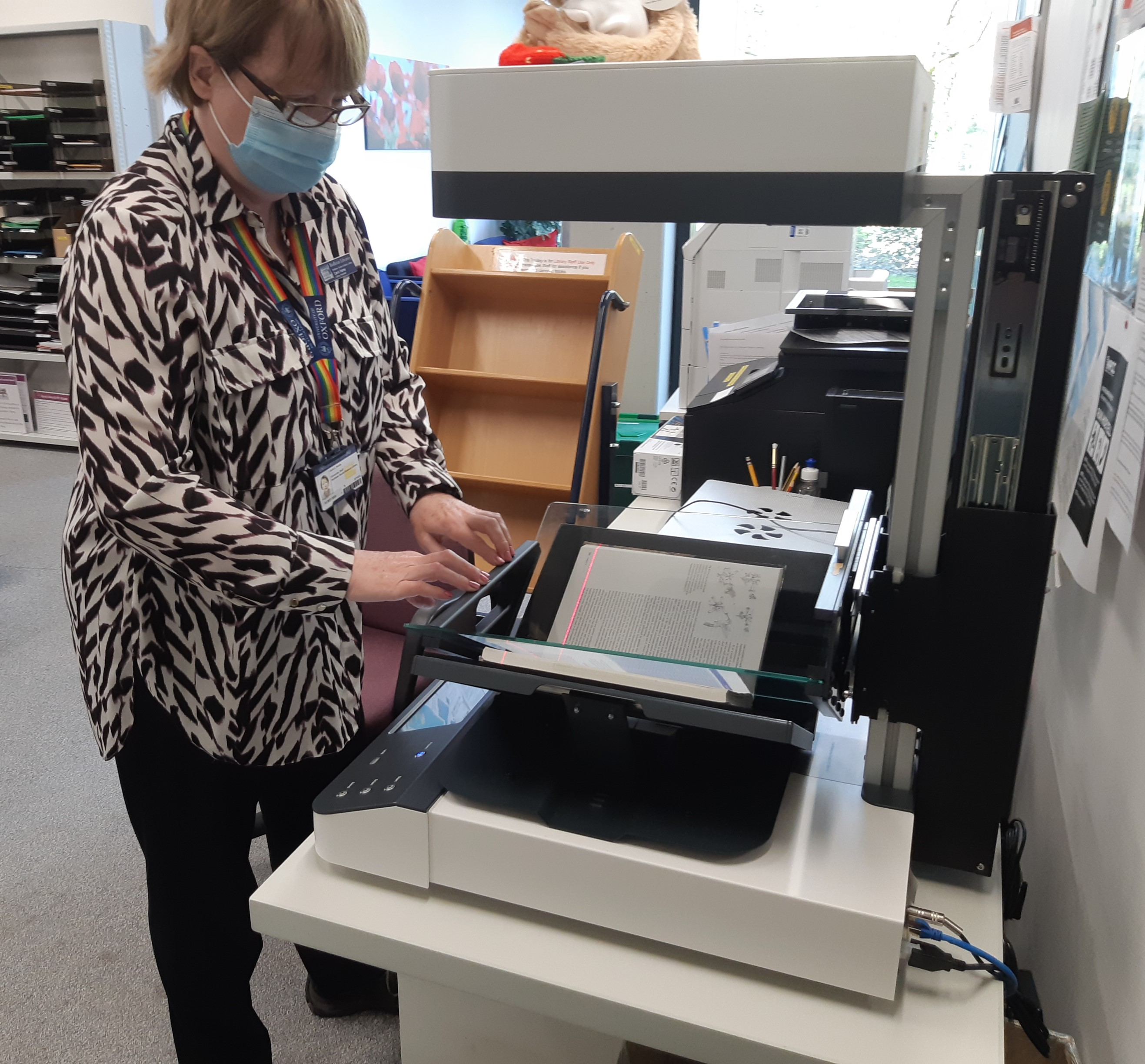 Staff member scanning a book on our scanner.