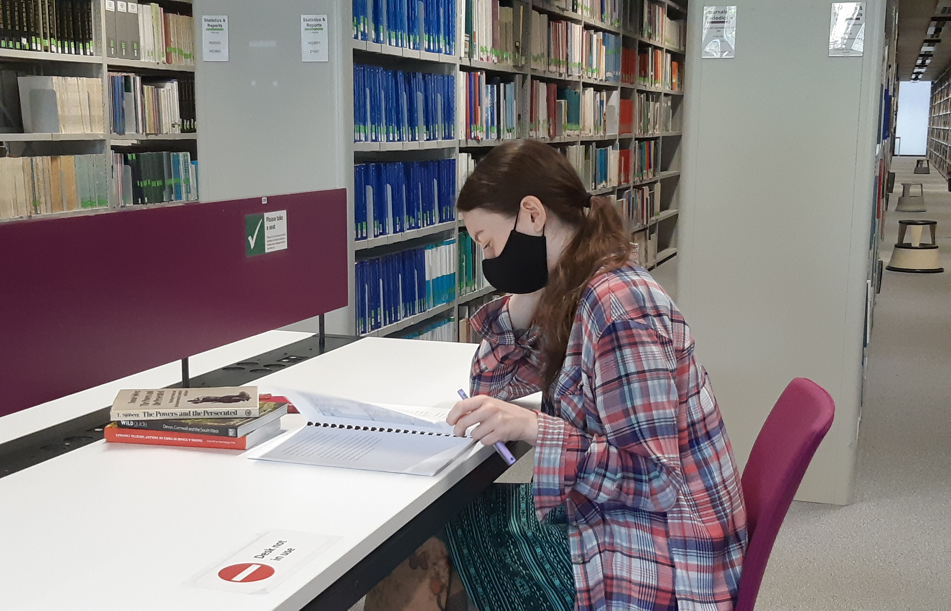 Student say studying (wearing a face mask) at a desk in the Social Science Library