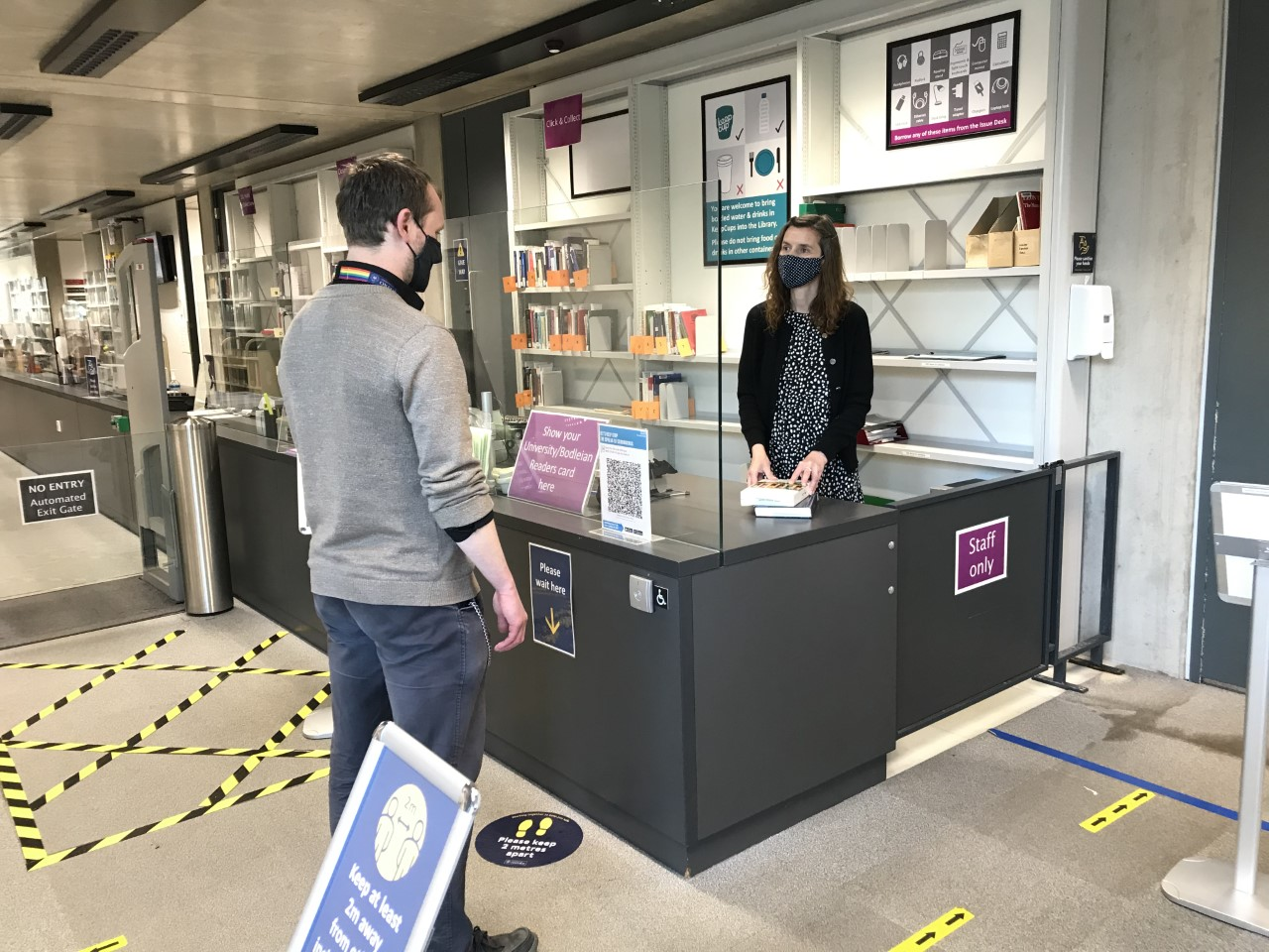 A staff member and reader stood at the SSL Issue Desk wearing face masks