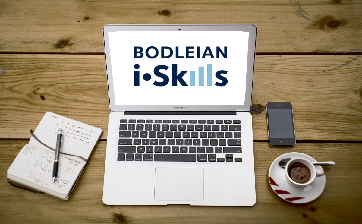 Open laptop on a desk with the words Bodleian iSkills on it. Adjacent to the laptop is a notebook and pen, phone and a cup of coffee.