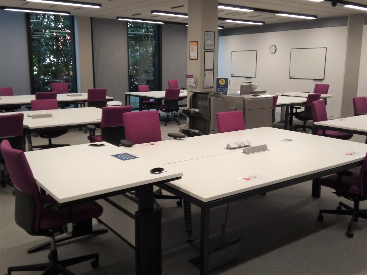 Photo of desks in the Central Graduate Study Room. Large desks with no partitions.