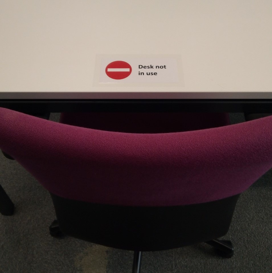 Photo of a sign on a desk which has a red no entry symbol on it and the words Desk no in use.