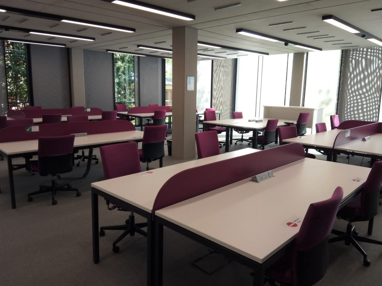 Photo of desks in the EGSR. Large desks that have a partition down the centre, height adjustable seating.