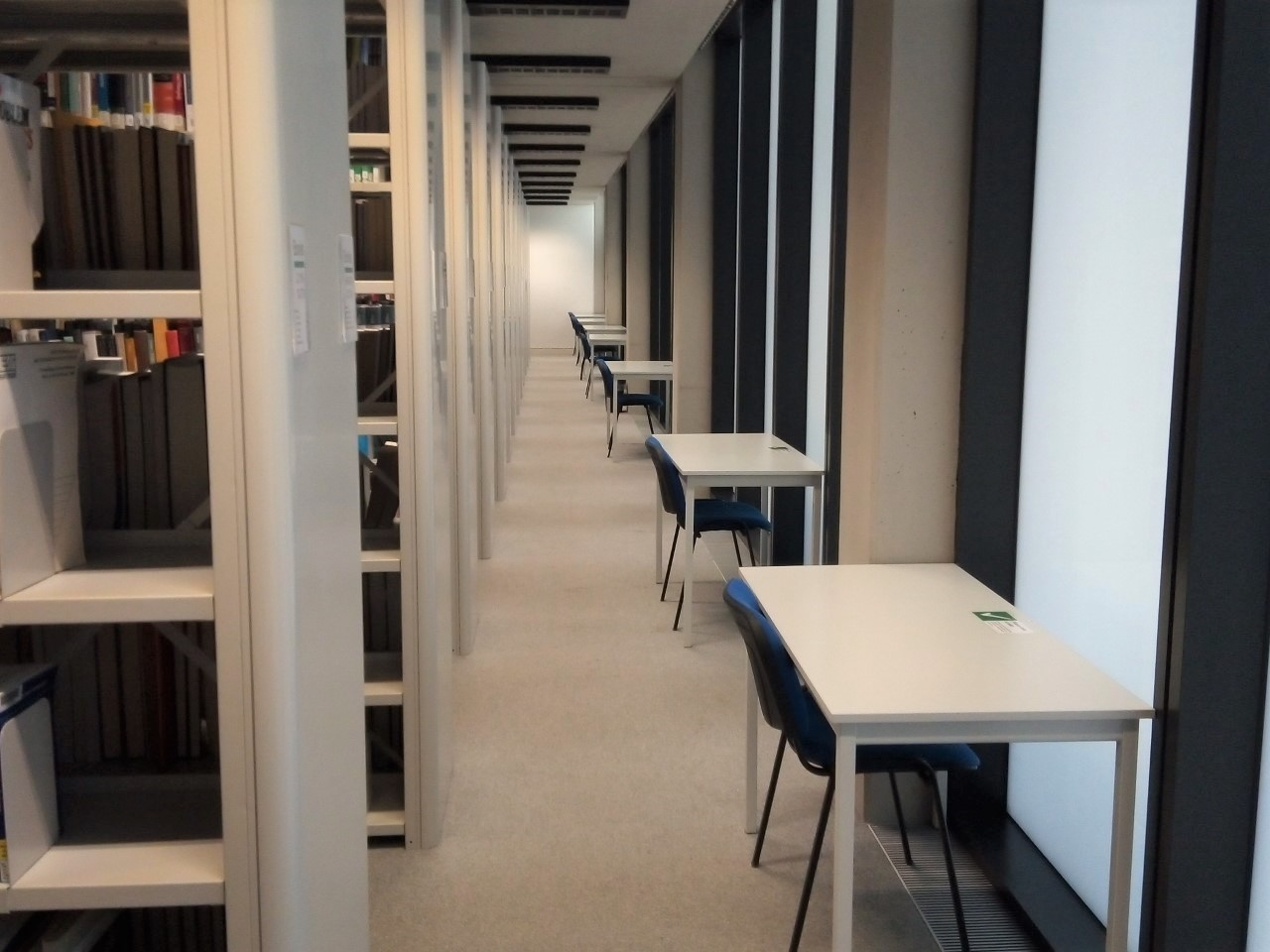 Photos of individual desks, spaced out along a wall/windows adjacent to the St Cross Building.