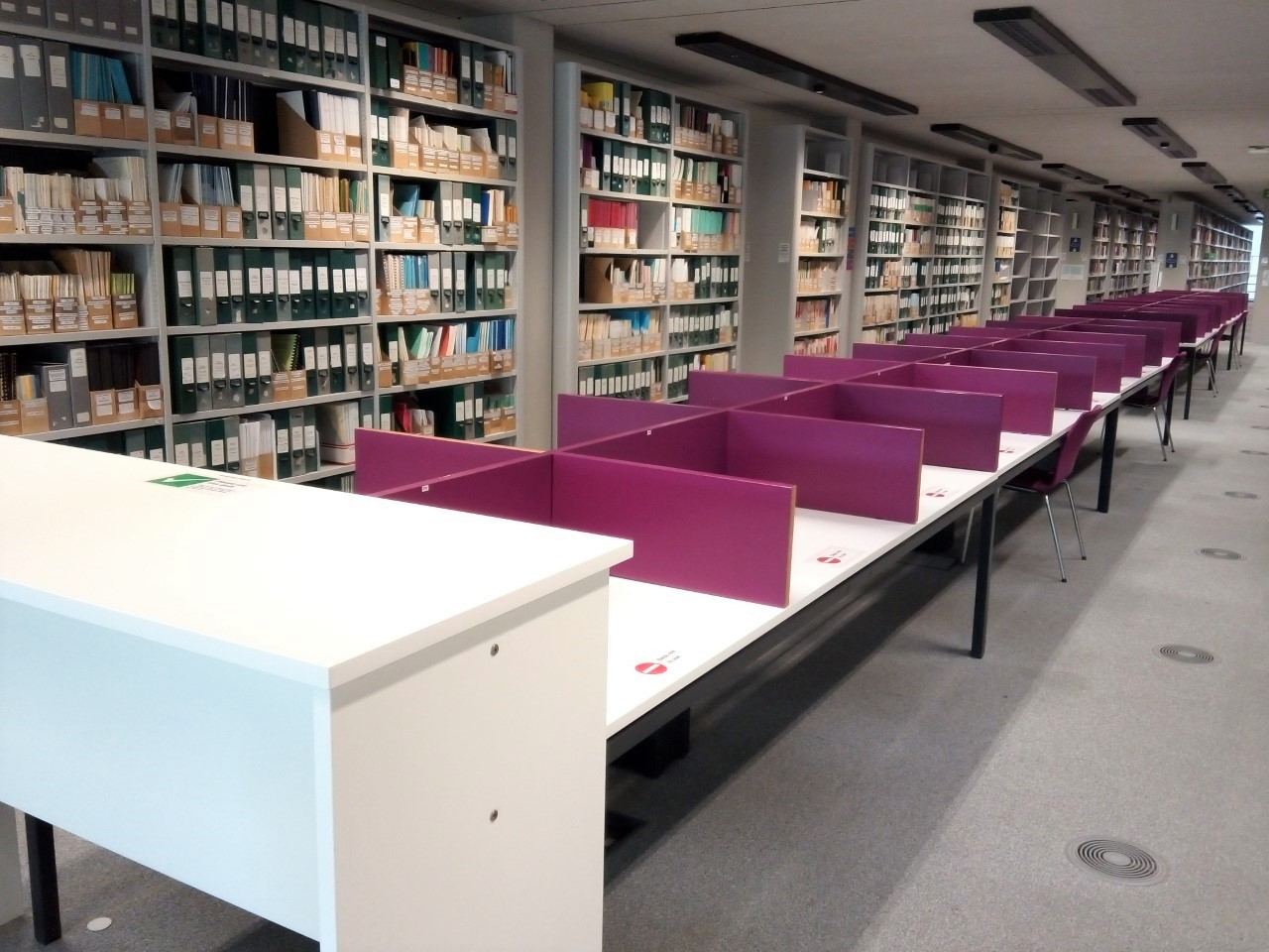 A photos of the desks in front of the Central Graduate Study Rooms. There are individual spaces in a row and all are partitioned on all sides.