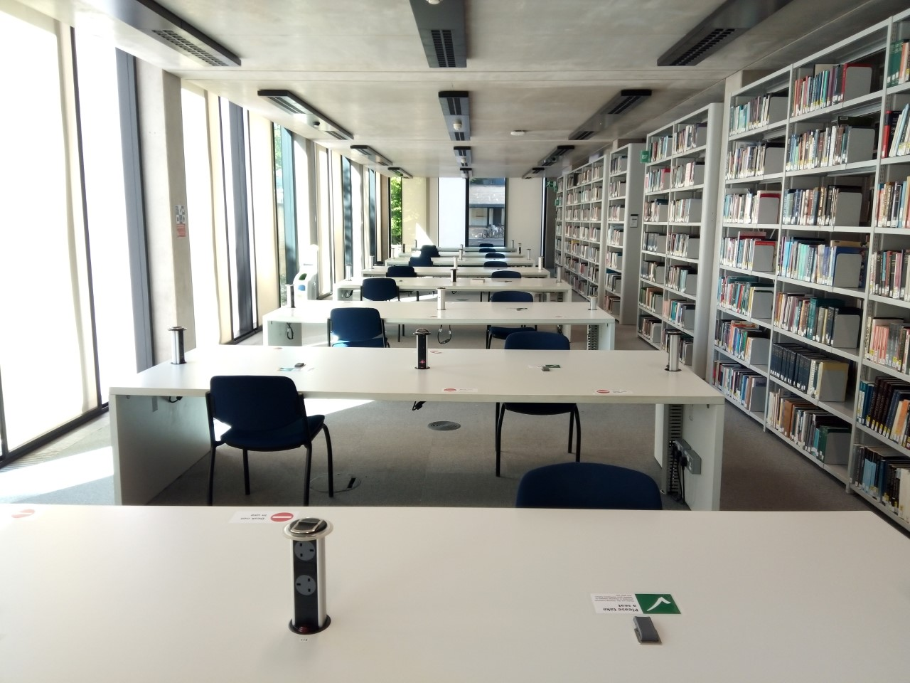 A photo of our open plan seating area to the left of our issue desk. Desks are large tables.