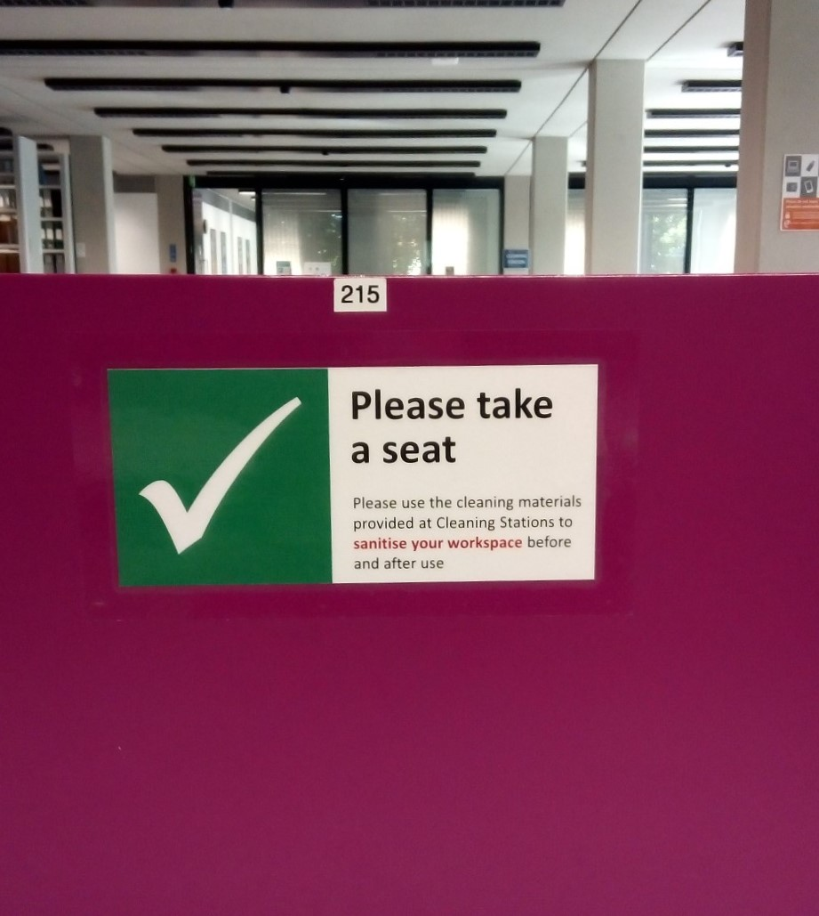 Photo of a notice on a desk, which has a white tick in a green box and the words Please take a seat.