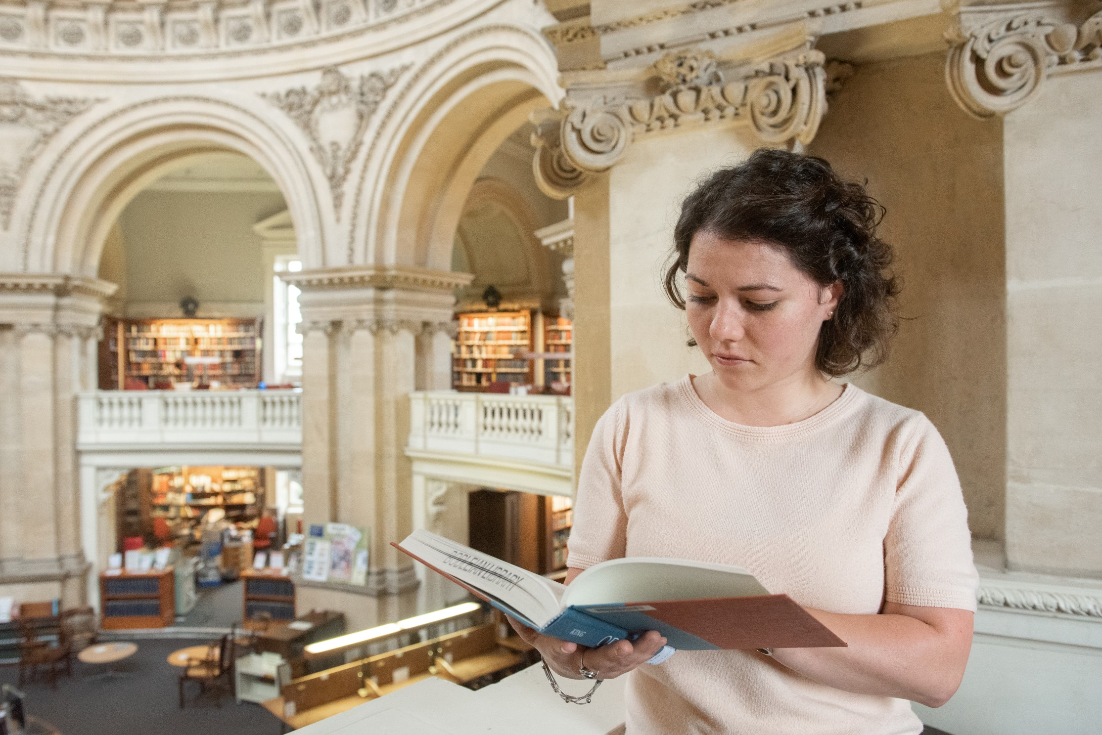 Person stood reading a book in the reading rooms of the Radcliffe Camera.