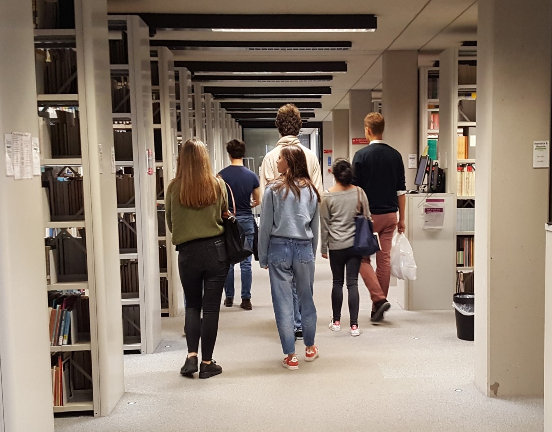 Group of students walking through the SSL bookshelves on a tour of the library.