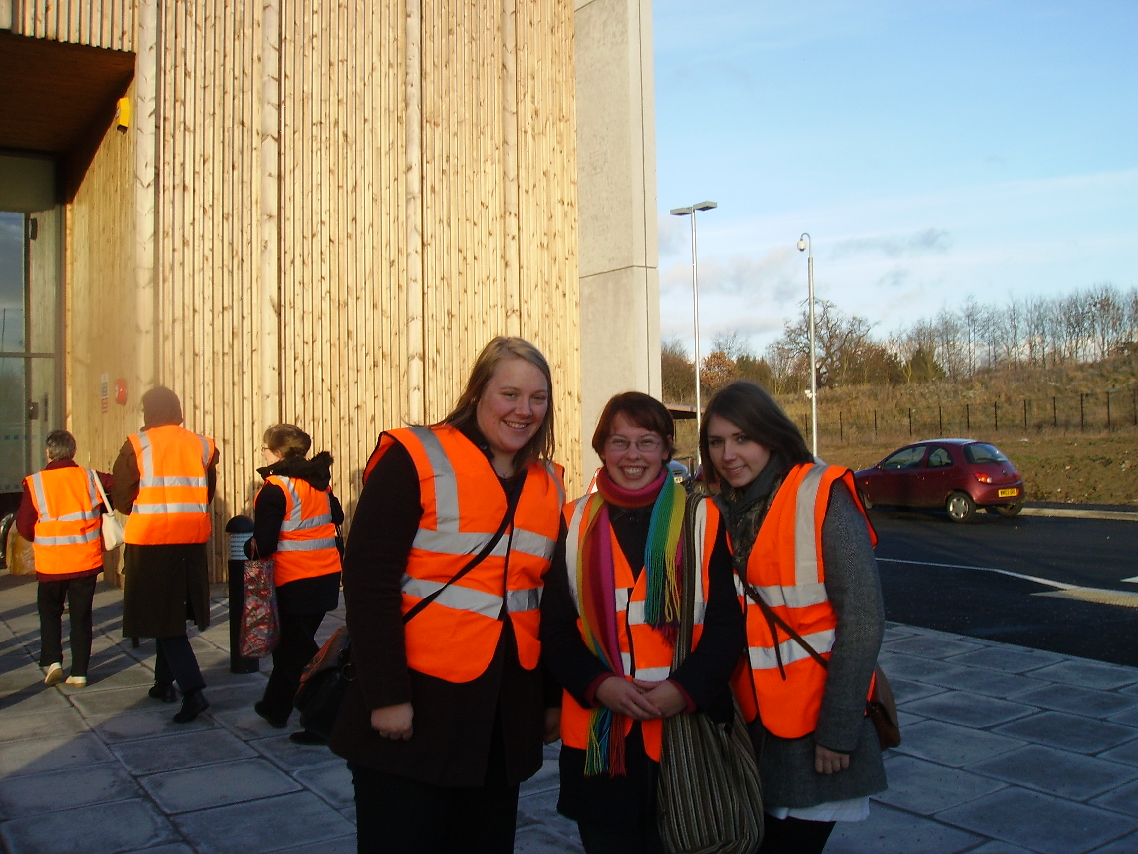 Visit to the Book Storage Facility, Swindon - three trainees outside the front door in high-visibility jackets