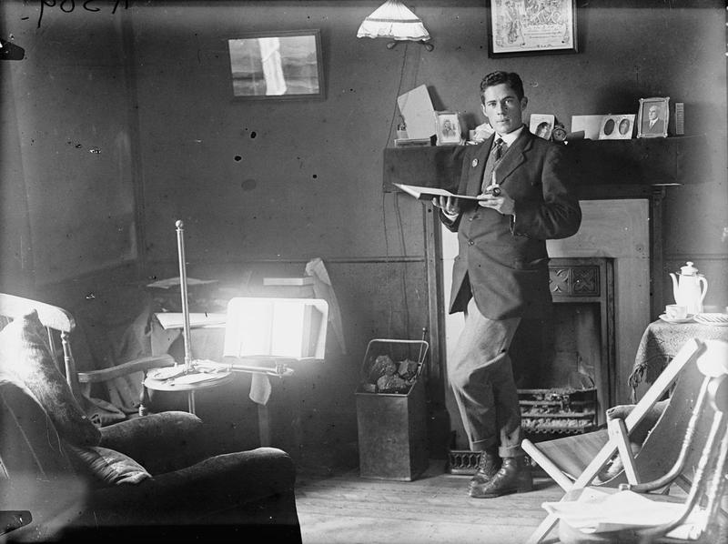 """""""A student's room in Keble College, Oxford. The student is one of 18 at present in residence and has received his discharge from the Army (owing to health), after a period of fighting in Egypt and France - his discharge is to be seen hanging over the mantle-shelf where he is standing.""""  Image available under the IWM Non Commercial Licence, © IWM (Q 30292)."""